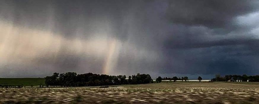 Mørke skyer og halv regnbue over mark