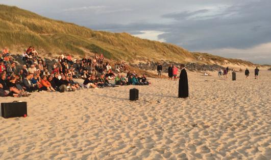 Forsamling sidder på skrænt ved stranden og kigger på præst