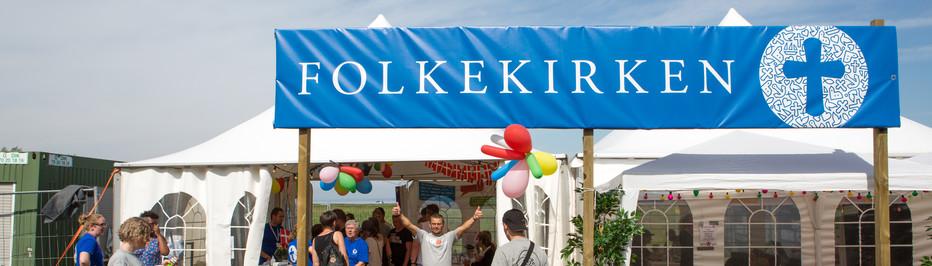 Skilt med Folkekirken + logo foran telte med balloner, lyskæder og flag