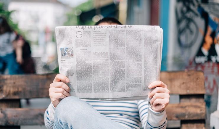 Person sidder på bænk og læser avis foran hovedet