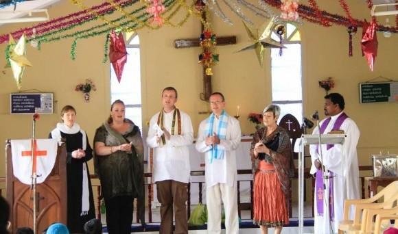 Seks personer i forskellige præstekjoler står på række i festlig pyntet kirkerum