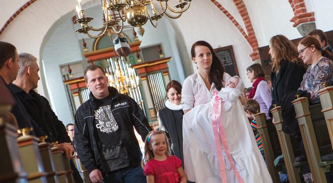 Kvinde med dåbsbarn i arme og familie på vej ned af kirkegulvet