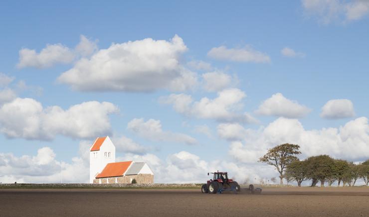 Traktor på mark omkring kirke