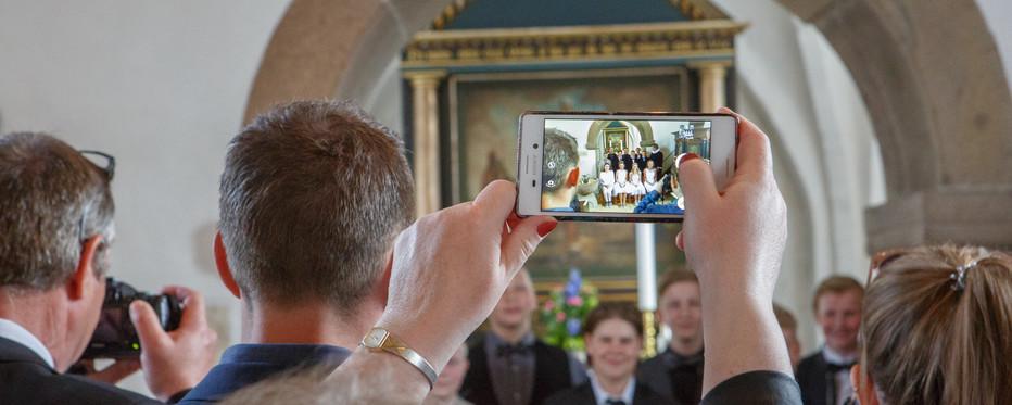 Kvindehænder, der holder iphone og tager billede af et hold konfirmander