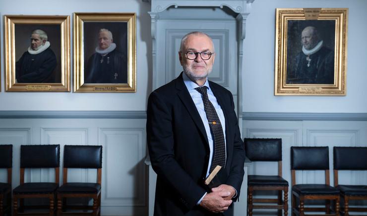 Biskop i skjorte, slips og jakkesæt holder bog foran maven i lokale med malerier af præster på væggen