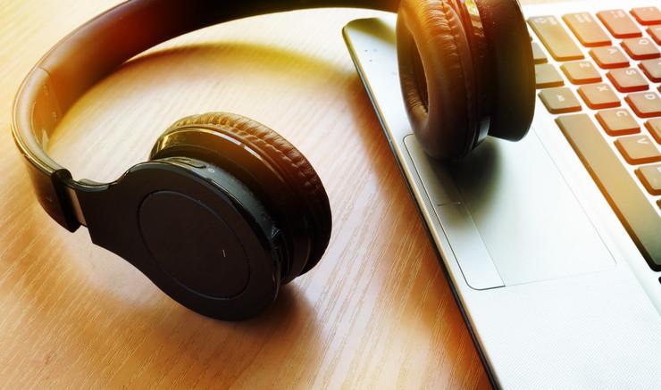 Høretelefoner ovenpå tastatur på bærbar