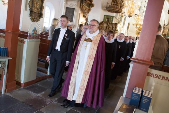 Biskop og præster går ud af kirke